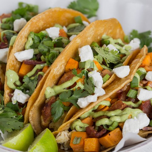 Plate of four tacos stuffed with bacon, sweet potatoes and goat cheese