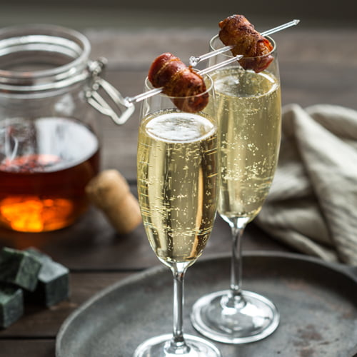 Two champagne flutes filled with bacon washed bourbon cocktail and garnished with crispy bacon