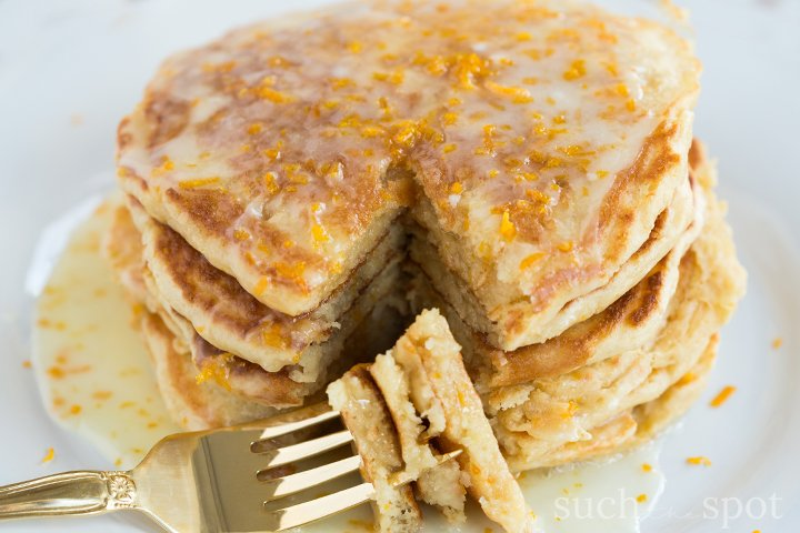 Stack of fluffy pancakes with thick mimosa glaze drizzling down the sides.