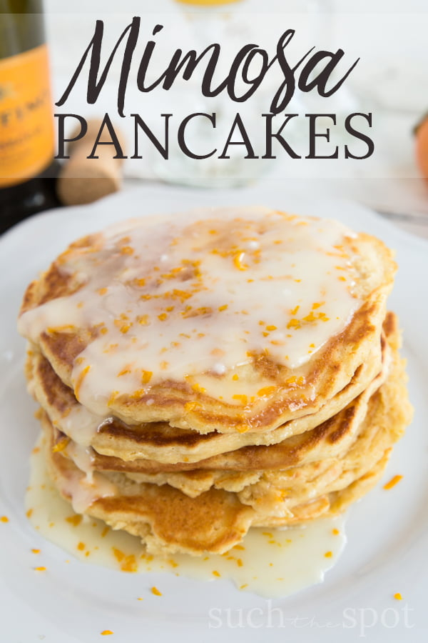 Plate of fluffy buttermilk pancakes with mimosa glaze drizzling down the sides.