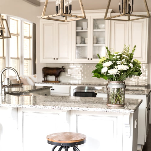 Clean and organized kitchen with a vase of white flowers on the counter