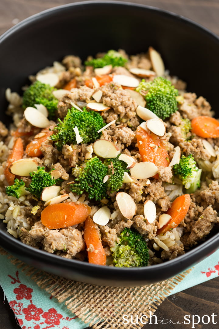 A healthy beef and broccoli alternative, this is a bowl of ground turkey and broccoli studded with carrots and garnished with toasted almonds over rice.
