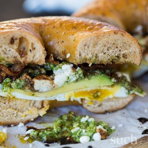 Balsamic Pesto Bacon Egg Breakfast Sandwich with oozing pesto and crumbled bacon on a plate.