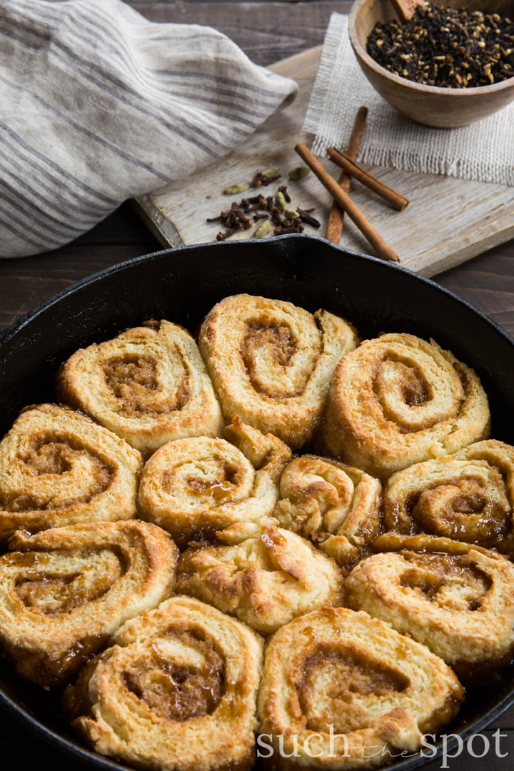 One dozen quick chai spiced skillet sticky buns in a cast iron skillet.
