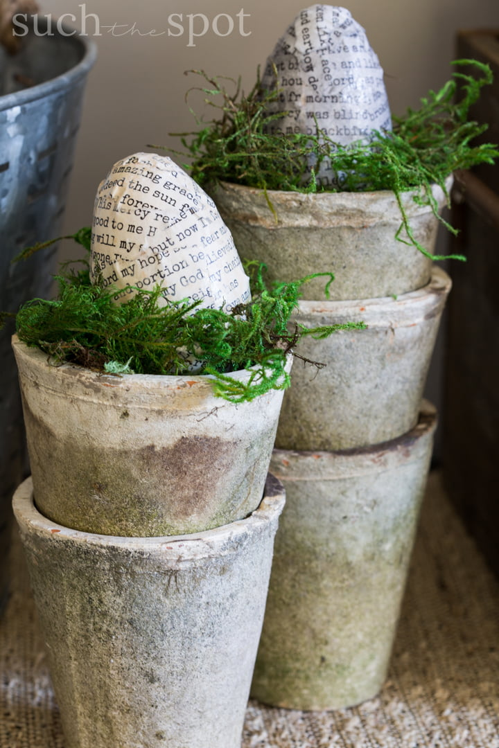 Decoupaged eggs in a rustic clay pot a with moss.