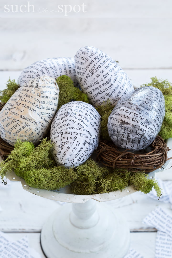 Decoupaged eggs on a cake platter with moss and grapevine