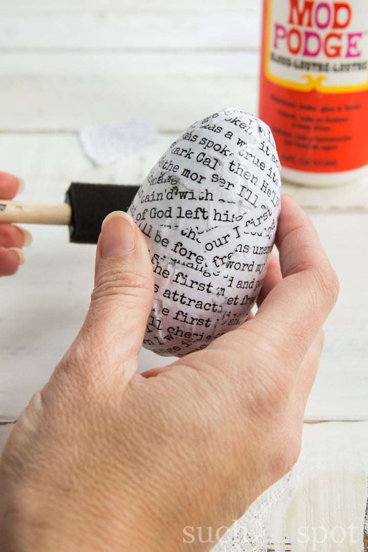 Strips of torn paper with words in typewriter font on a wooden egg