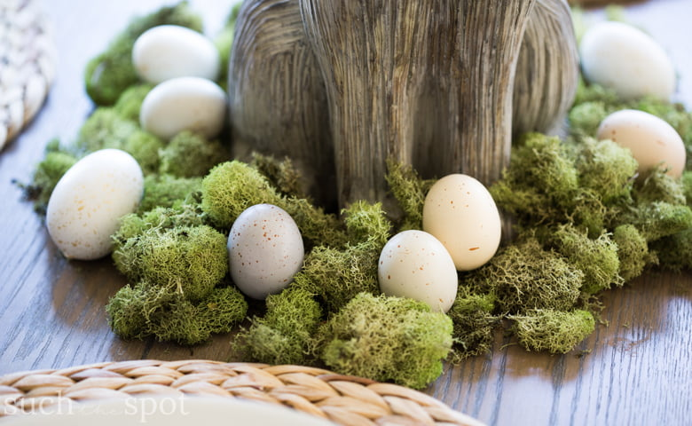 An easy and casual spring table set with four places. A ceramic bunny centerpiece is surrounded by faux Easter eggs.