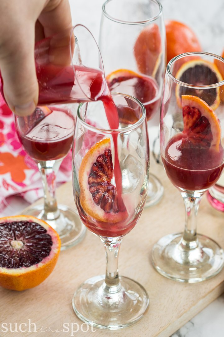 Four champagne flutes filled with elderflower blood orange mimosas