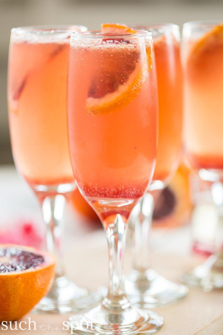 Four champagne flutes filled with elderflower blood orange mimosas
