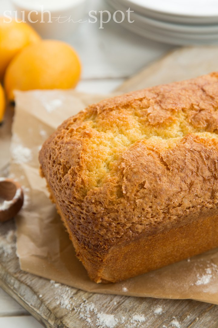 Loaf of lemon pound cake on a cutting board with lemons in the background