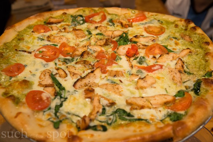 Pizza topped with grilled chicken and tomatoes