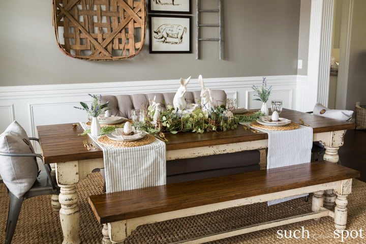 Chunky farmhouse dining table decorated for spring with bunnies, greenery and lavender