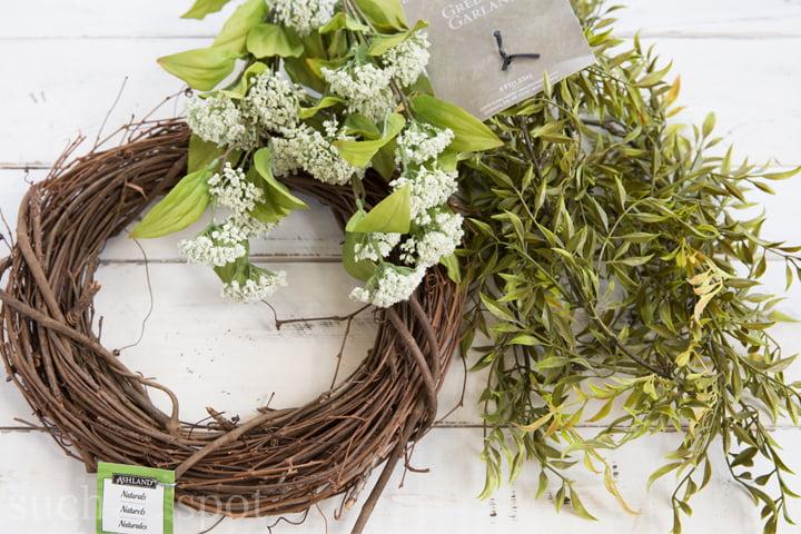 Grapevine wreath, white floral bush and faux greenery vine on a white shiplap board