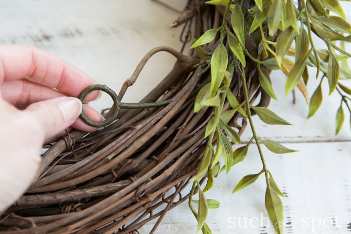 Grapevine wreath with wild faux greenery garland placed on top