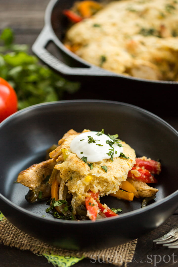 red and orange bell pepper strips topped with cornbread, sour cream and chopped cilantro