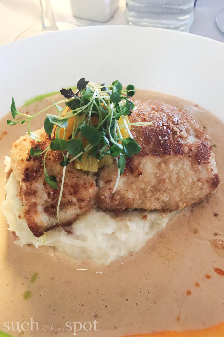 a filet of grilled Moonfish served over a bed of mashed potatoes and garnished with microgreens