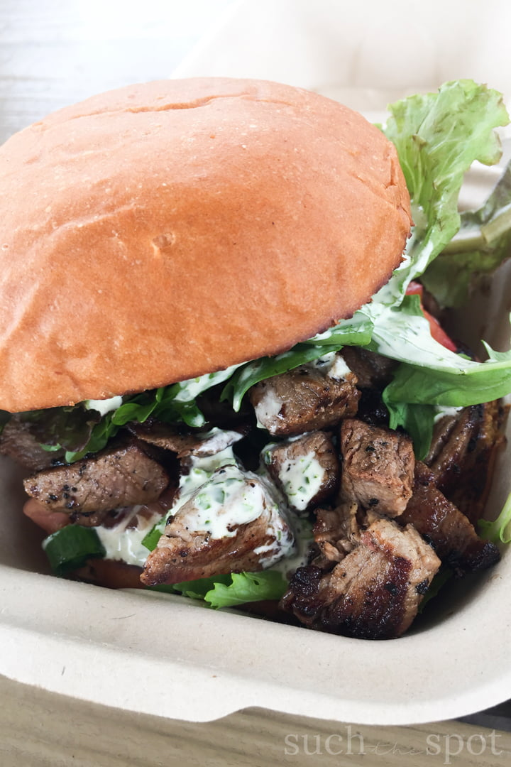 Grilled steak sandwich on bun garnished with lettuce