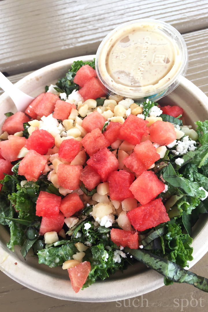 Quinoa bowl with honey mustard massaged kale, topped with diced watermelon, feta cheese and chopped macadamia nuts