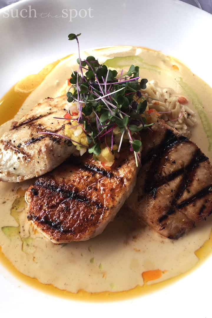 Trio of grilled fish medallions served over a bed of lavender orzo and garnished with microgreens