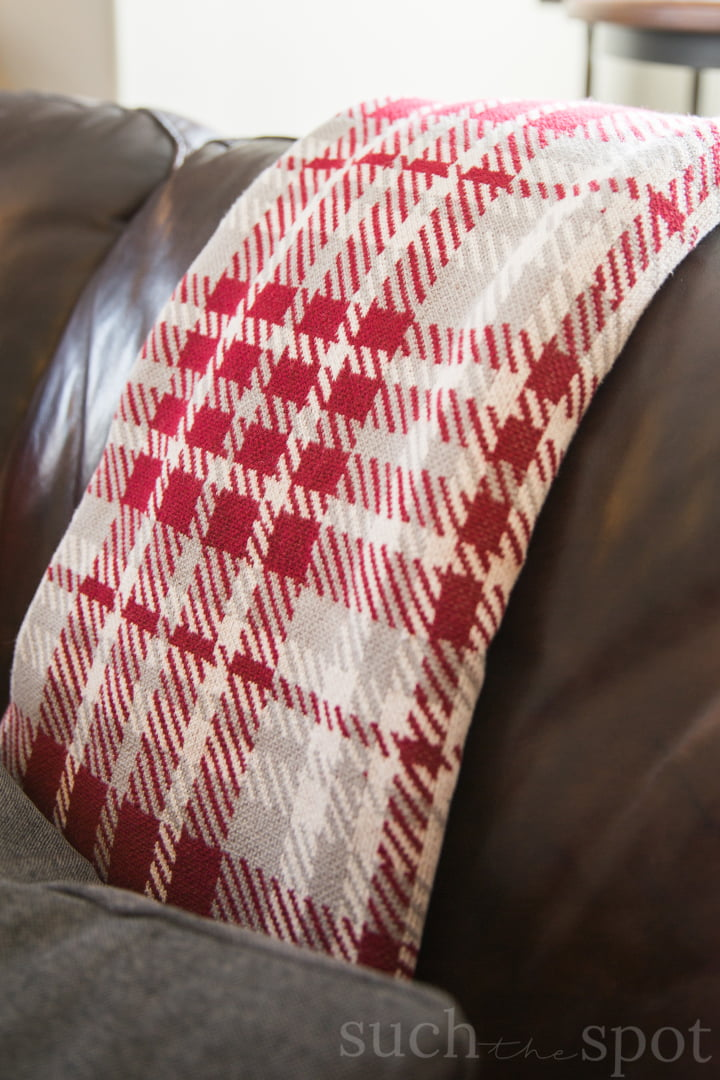 Red and gray houndstooth throw blanket draped over brown leather couch