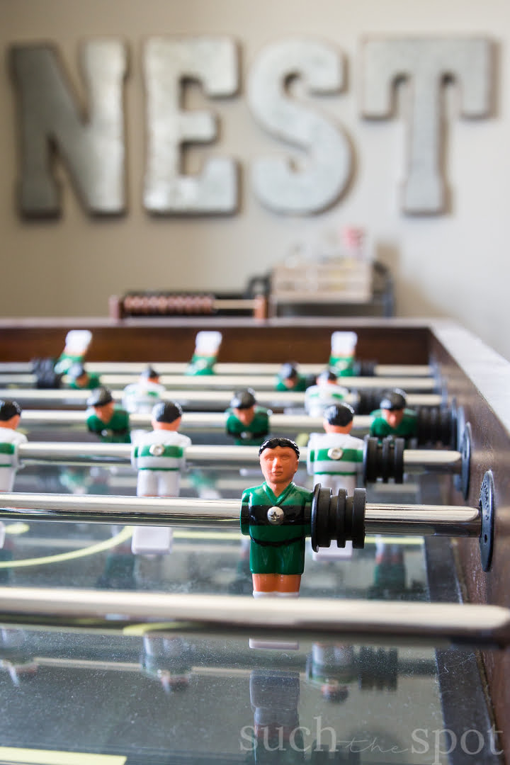 Foosball player close up with metal word on wall in background that says NEST
