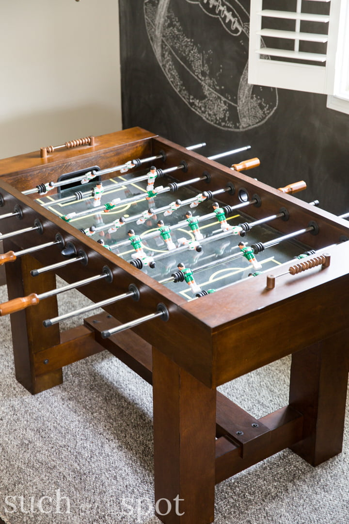 Aerial view of American Heritage foosball table with chalkboard wall in background