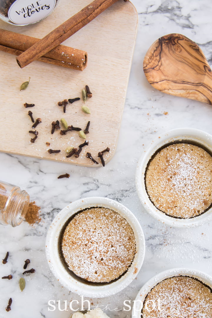 Individual chai spice pudding cakes in white ramekins with cloves scattered on cutting board