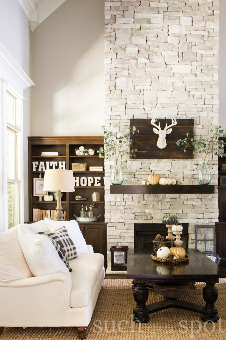 Gray stacked stone two-story fireplace with white couches and fall decor