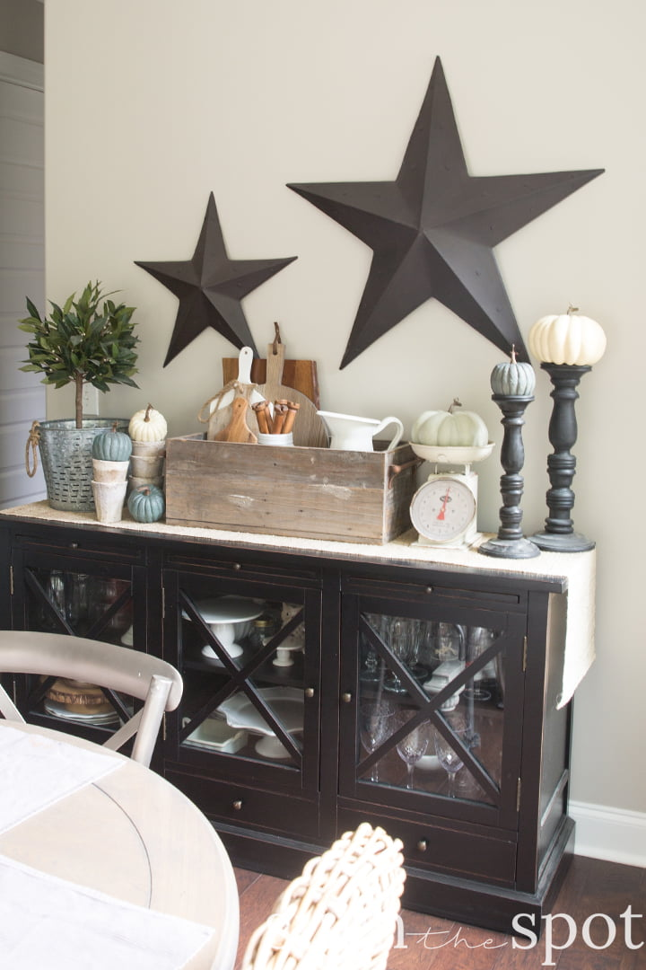 Black wood buffet table with rustic metal stars and a small round farmhouse table with mismatched chairs