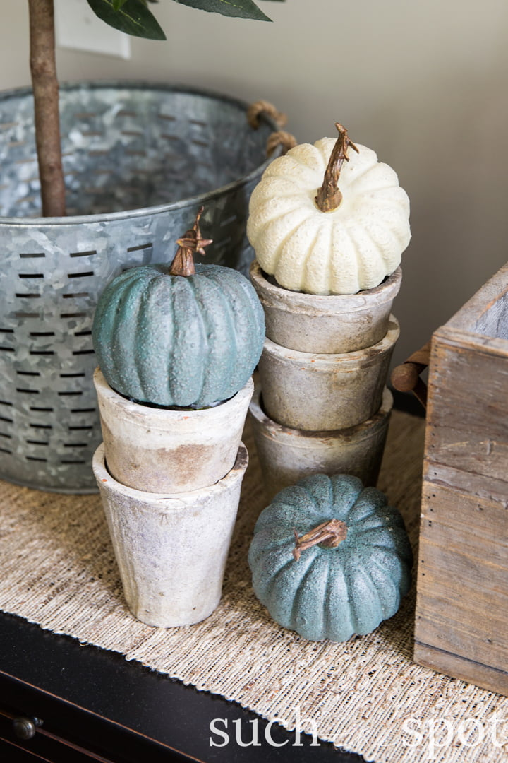 Gray and white faux pumpkins stacked in rustic ceramic pots
