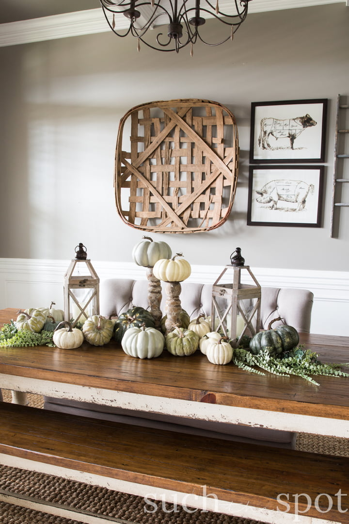chunky farmhouse dining table with pumpkins, lanterns and greenery as centerpiece