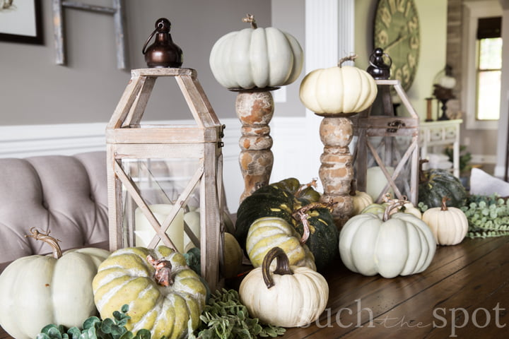 Fall centerpiece with lanterns, neutral green and white pumpkins and sprigs of greenery.