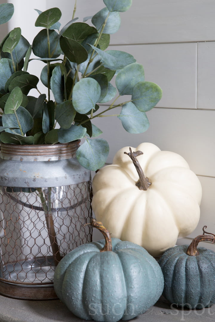 White pumpkin stacked on a smaller gray pumpkin for fall. A jar with chickenwire holds eucalyptus leaves.