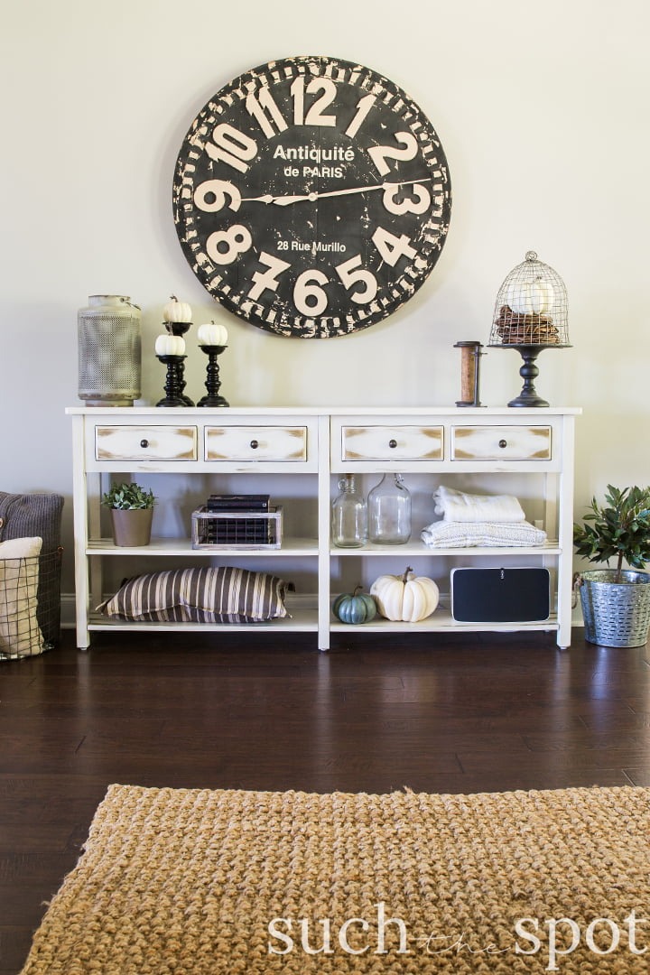 Farmhouse console table with oversized clock on wall decorated for fall with neutral pumpkins and other fall decorating ideas
