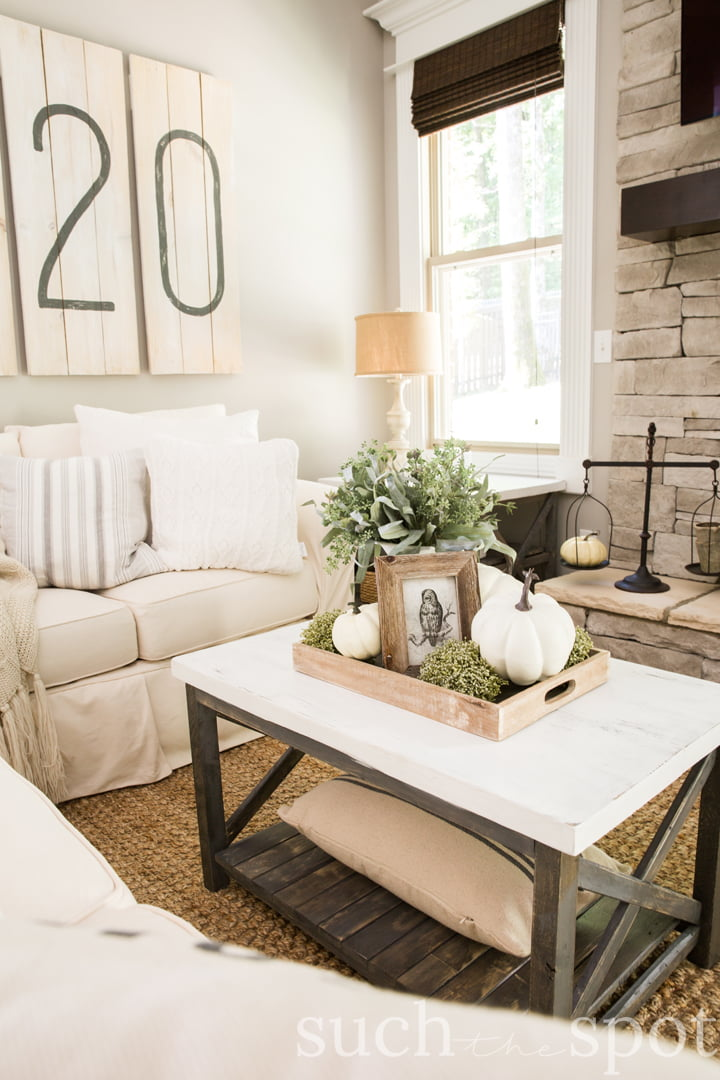 Several shades of white on white come together in this cozy family room with a white couch, white pillows and fall decorating ideas on the coffee table