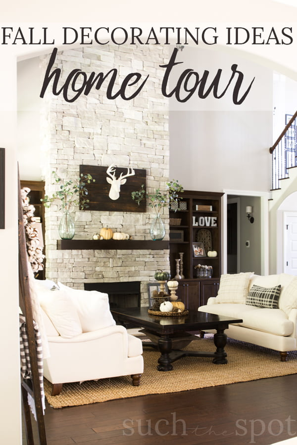 large room with stone stacked fireplace, white couches and fall decor