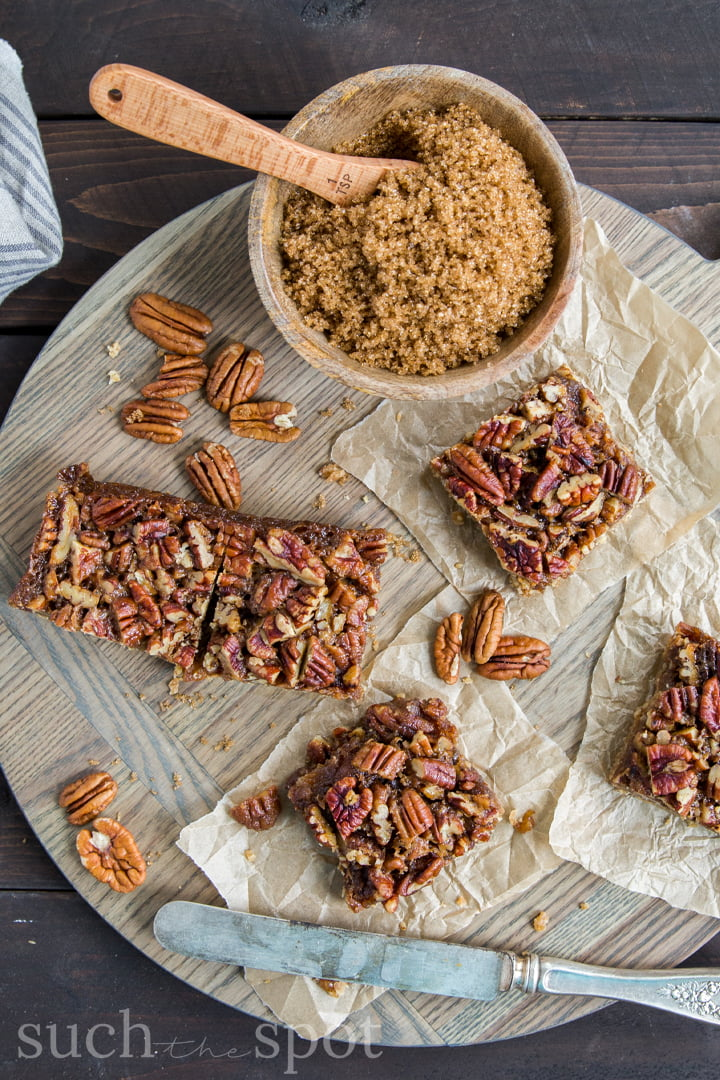 Sliced chewy pecan shortbread bar squares on parchment paper