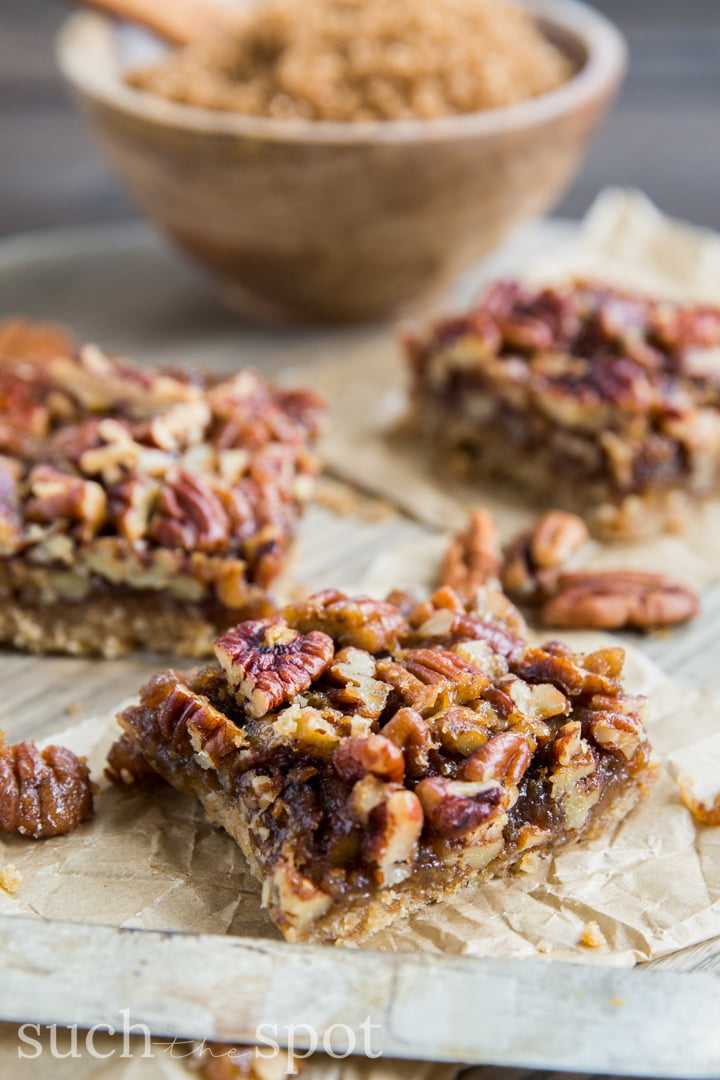 Chewy pecan shortbread bar squares stacked on a parchment paper square