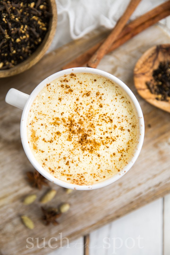 Pumpkin pecan chai latte topped with bourbon whipped cream in a large white mug