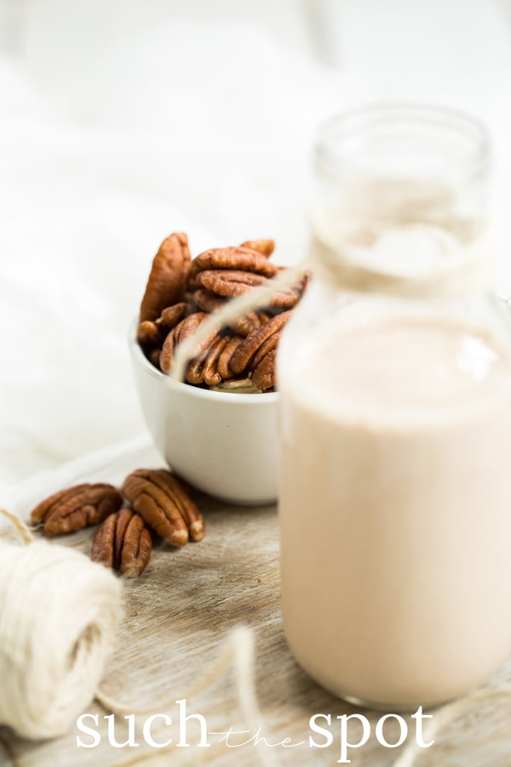 small jar of creamy homemade roasted pecan milk with pecans in the background