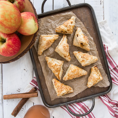 Golden brown easy apple turnovers on a baking sheet with cinnamon sticks and dusting sugar