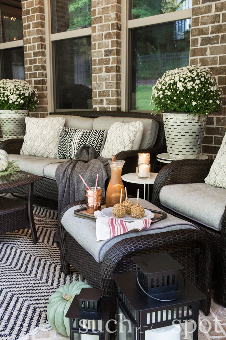 cozy fall patio space decorated with rugs, blankets, candles and fall foliage