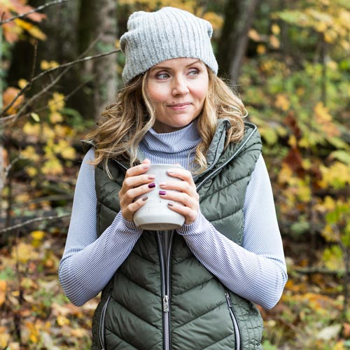 girl wearing cute puffer vest outfit and holding a mug