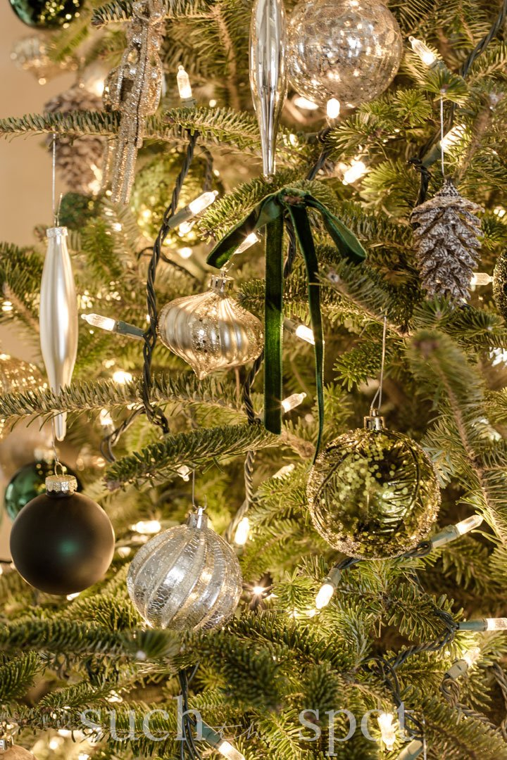 green and gold christmas ornaments with green velvet bows on christmas tree