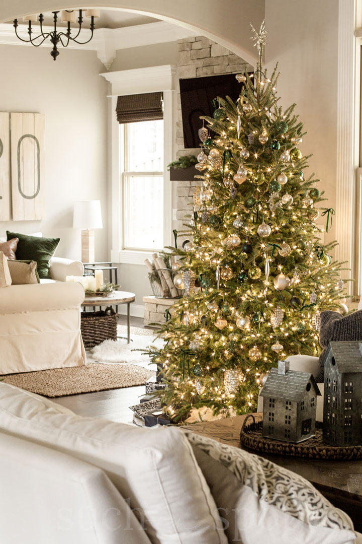 Green and gold ornaments on Christmas tree with white lights
