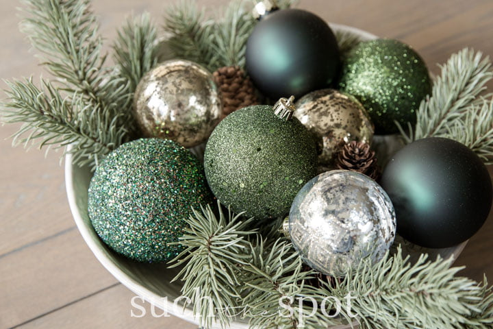 Christmas ornaments in decorative bowl with greenery