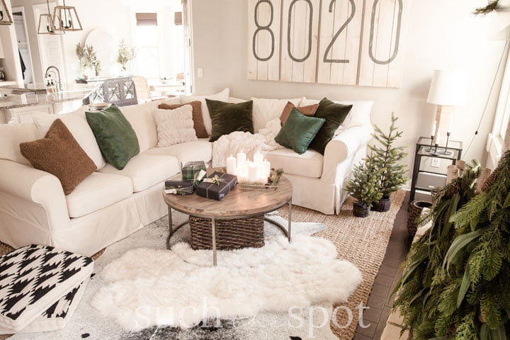 Cozy family room with sectional and green velvet pillows