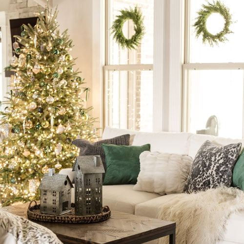 Green velvet pillows with faux fur accessories in living room decorated for Christmas