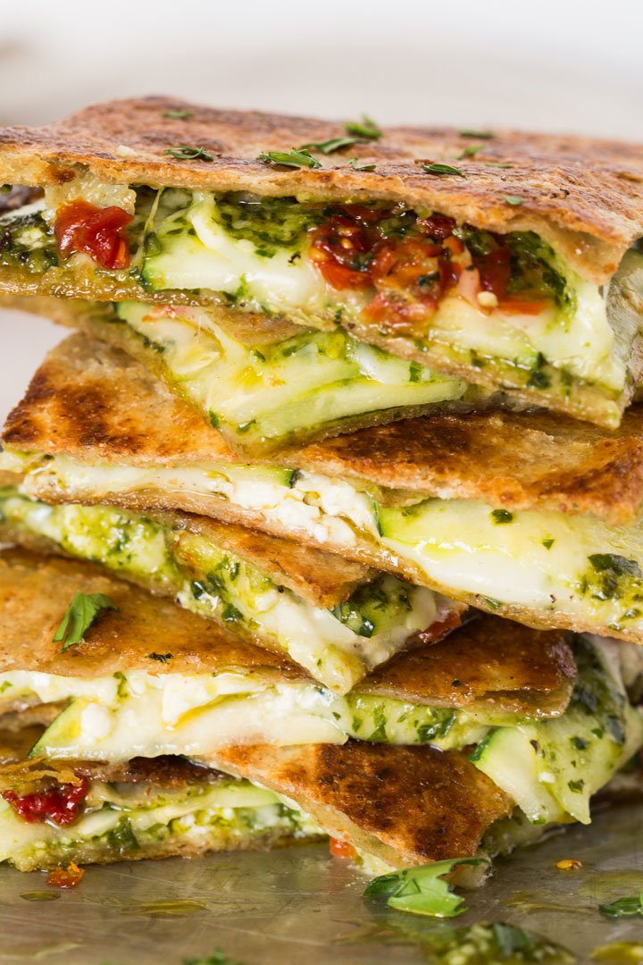 Pesto Zucchini quesadillas piled high on a sheet pan